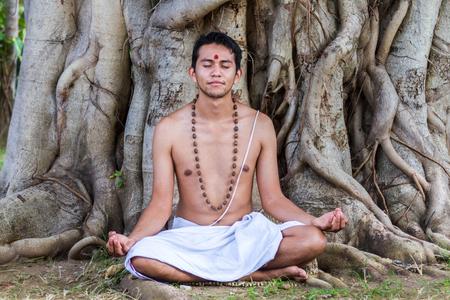 A young Hindu brahmin sits in meditation under a banyan tree.