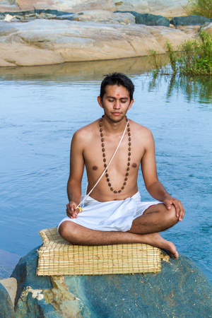 dhyana: A young Hindu brahmin sits in meditation on a river bank.