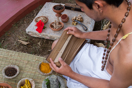 A young brahmin reads an ancient Hindu text surrounded by natural medicinal ingredients. 版權商用圖片