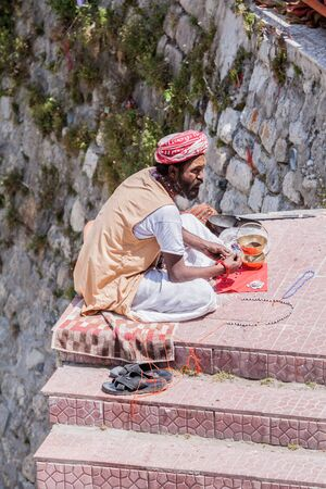 BADARINATH - INDIA, JUNE 5th - A sadhu sells holy beads on the steps near the temple of Badarinath in North India on June 5th 2013