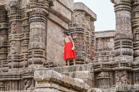 KONARK, INDIA OCT 8th 2010  A young girl in a red dress at the Konark Temple in East India.