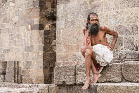 dhoti: KONARK, INDIA OCT 8th 2010  An old man sitting on the steps of the Konark Temple in East India.