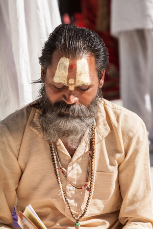 vedas: GANGOTRI, INDIA - MAY 23rd - A Hindu priest sits in the temple courtyard to read Vedic scriptures in Gangotri on 23rd May 2013. Editorial