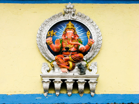 A painted sculpture of the Hindu god Ganesh on the wall of a temple. Foto de archivo