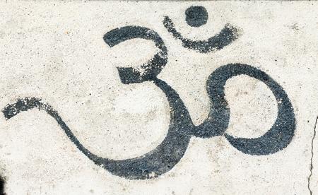 moksha: A black om on a white wall
