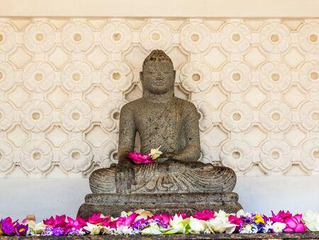 A statue of Buddha surrounded by lotus flowers, at Kelaniya, Sri Lanka