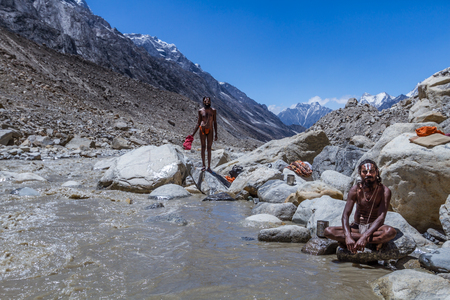 GAUMUKH, INDAI - CIRCA May 2013 - Hindu sadhus take a dip in the freezing cold waters at the source of the Ganges in Gaumkh circa May 2013, Gaumukh, India. Editorial