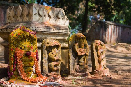 deities: A row of Hindu Naga deities decorated with flowers and kumkum in South India.