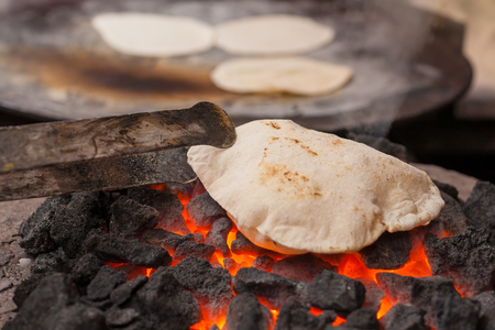 A roti (Indian flatbread) cooking on a coal fire.