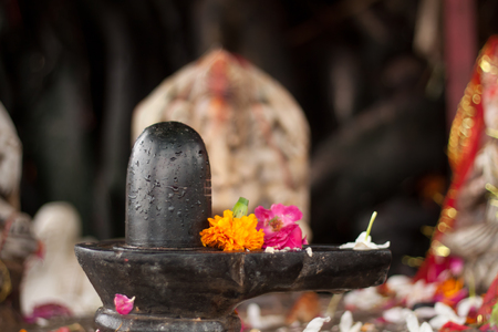 A small, black shiva-lingam made from stone and covered in flowers.