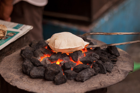 atta: A roti (indian flatbread) cooking on a coal fire.