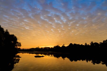 skyscape: Early morning sky over a river with colors from deep blue to orange. Stock Photo