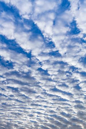 stratus: White puffy stratus clouds against a deep blue sky.