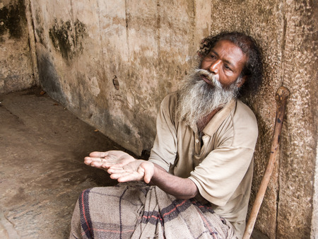 MELKOTE, INDIA - MAY 9th - An old Indian beggar waits for alms on a street corner on May 9th 2008 at Melkote, India.