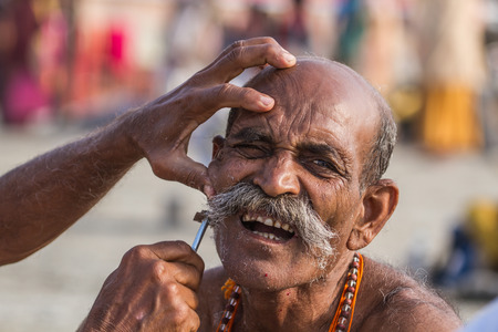 sadhu: ALLAHABAD, INDIA - FEB 14 - A Hindu pilgrim has his face shaved before taking a sacred bath during the festival of Kumbha Mela on February 14th 2013 at Allahabad, India.