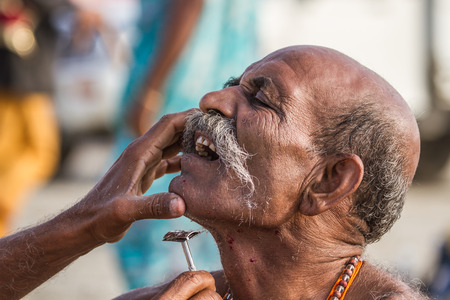 ALLAHABAD, INDIA - FEB 14 - A Hindu pilgrim has his face shaved before taking a sacred bath during the festival of Kumbha Mela on February 14th 2013 at Allahabad, India.