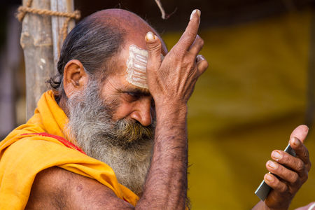 ALLAHABAD, INDIA - FEB 14 - A Hindu priest applies a sectarian marking to his forehead during the festival of Kumbha Mela on February 14th 2013 at Allahabad, India. Editorial
