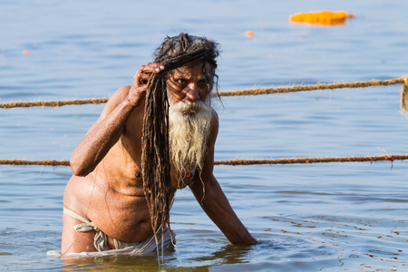 sadhu: ALLAHABAD, INDIA - FEB 14 - A Hindu sadhu takes a holy bath in the Ganges river during the festival of Kumbha Mela on February 14th 2013 at Allahabad, India.