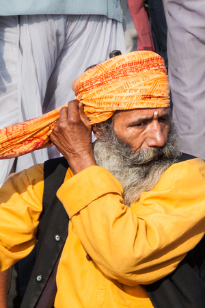 ALLAHABAD, INDIA - FEB 10th - An old sadhu winds a cloth around his head to make a turban at the Kumbha Mela on February 10th 2013 Editorial