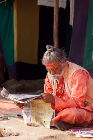 ALLAHABAD, INDIA - FEB 13 - An Hindu priest reads a newspaper in front of his tent during the festival of Kumbha Mela on February 13th 2013 at Allahabad, India.