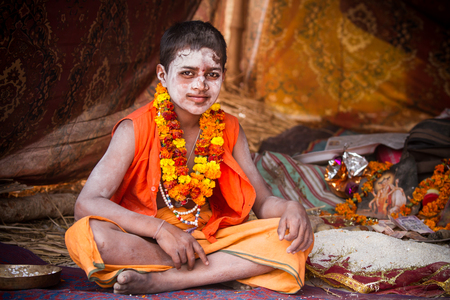 ALLAHABAD, INDIA - FEB 13 - A young Hindu priest sits inside of his tent during the festival of Kumbha Mela on February 13th 2013 at Allahabad, India.