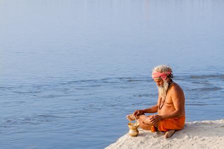 ALLAHABAD, INDIA - FEB 14th - A sadhu meditates on the banks of the Ganges at the Kumbha Mela on February 14th 2013