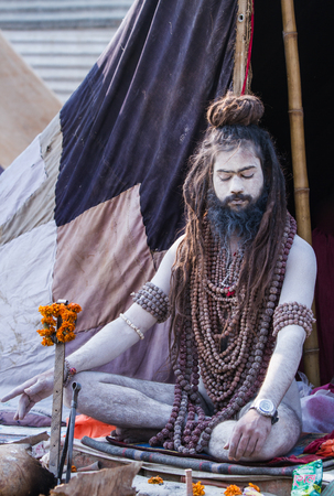 ALLAHABAD, INDIA - FEB 13 - A Hindu renunciate sits in meditation in front of his tent during the festival of Kumbha Mela on February 13th 2013 at Allahabad, India.