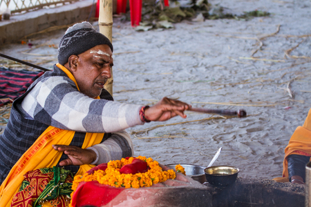 ALLAHABAD, INDIA - FEB 9 - A Hindu priest offers oblations into a sacred fire during the festival of Kumbha Mela, February 10th 2013 at Allahabad, India. Editorial