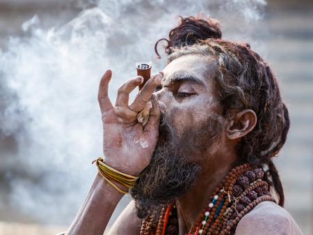 ALLAHABAD, INDIA - FEB 13 - A Hindu sadhu smokes a hash pipe during the festival of Kumbha Mela on February 13th 2013 at Allahabad, India. Editorial