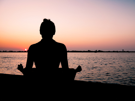 A young brahmin boy sits in a riverbank and meditates at sunset. Stock fotó