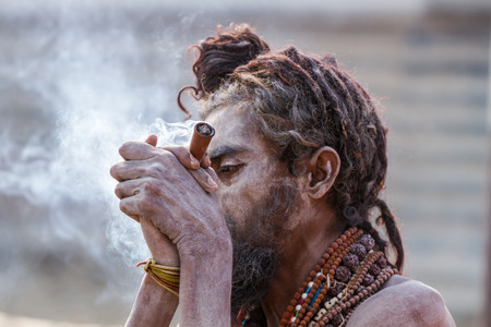 ALLAHABAD, INDIA - FEB 13 - A Hindu sadhu smokes a hash pipe during the festival of Kumbha Mela on February 13th 2013 at Allahabad, India. Editorial