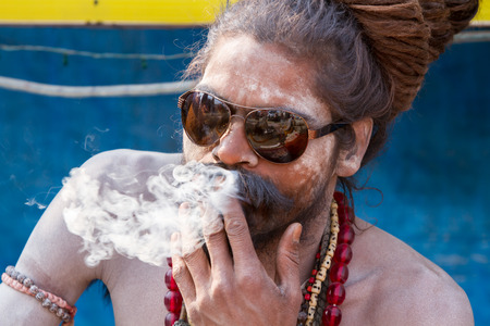 ALLAHABAD, INDIA - FEB 13 - A Hindu sadhu smokes a cigarette during the festival of Kumbha Mela on February 13th 2013 at Allahabad, India.