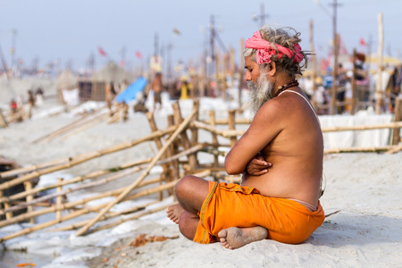 sadhu: ALLAHABAD, INDIA - FEB 14 - A Hindu pilgrim sits in meditation on the banks of the holy river during the festival of Kumbha Mela on February 14th 2013 at Allahabad, India.
