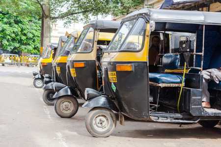 three wheeler: MYSORE, INDIA - JULY 24th 2010 - A row of auto rickshaws waiting for passengers.
