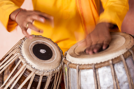 A young boy playing on traditional Indian tabla drums.