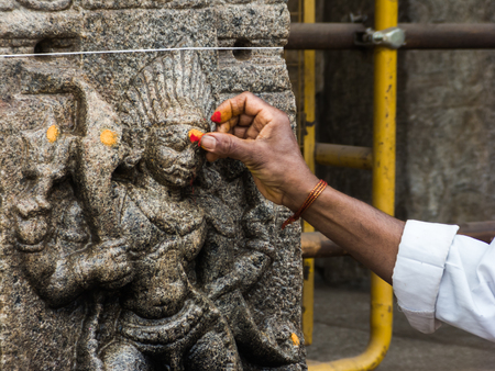 devotee: A devotee places red powder on a carving of Kala Bhairava at the temple of Nanjangud, South India.