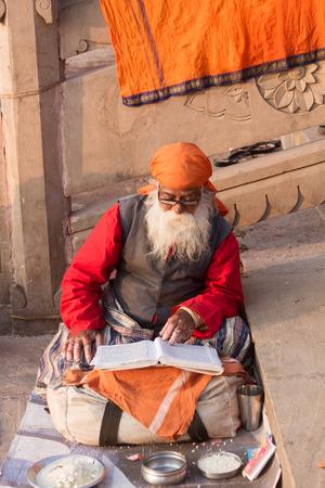 benares: VARANASI, INDIA - FEB 18 - An old sadhu in Varanasi reading holy scripture on February 18th 2013