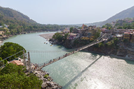 river banks: A photo of the Rishikesh Valley from the Lakshman Jhula iron suspension bridge across the River Ganges in the holy city of Rishikesh, North India.