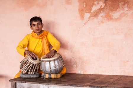 RISHIKESH INDIA, 13th AUGUST 2010  A young boy playing on traditional Indian tabla drums. Editorial