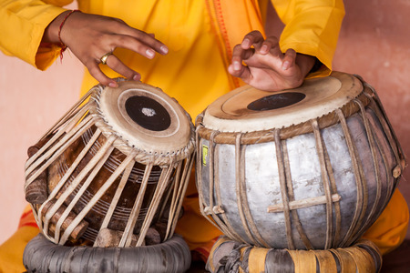 A young Indian monk plays the tabla drums.