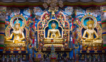 A monastery altar with deities of Padmasambhava, Buddha and Maitreya. Stock Photo