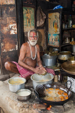 PURI, INDIA , OCTOBER 9th 2010 - An old man fries food in a wok in a roadside stall in East India.