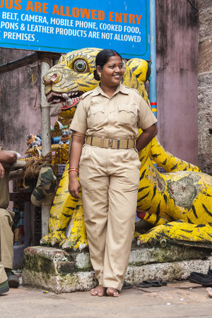 femme policier: PURI, INDIA, OCTOBER 9th 2010 - An Indian policewoman stands outside the temple of Jagannatha in Puri.