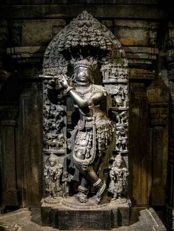 A deity of Krishna carved from black stone.