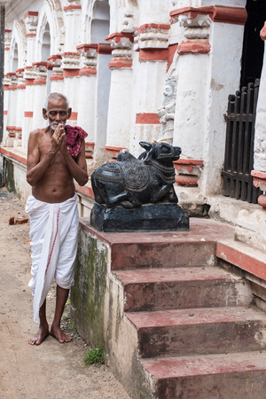 dhoti: PURI, INDIA – OCTOBER 9th 2010 – An old man praying outside a temple of Shiva in East India.