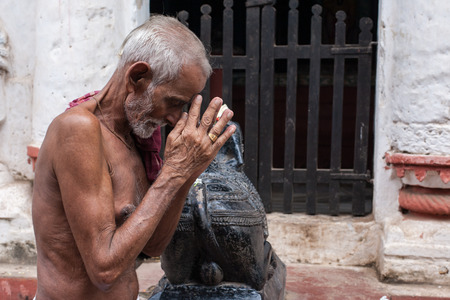 puri: PURI, INDIA, OCTOBER 9th 2010 - An old man praying outside a temple of Shiva in East India. Editorial