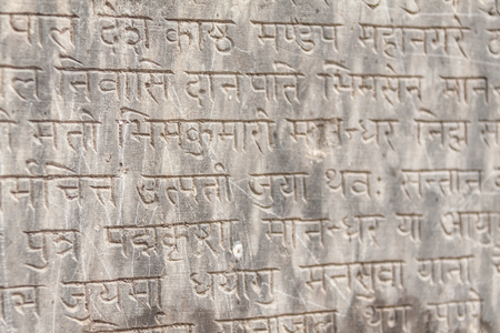 Ancient Sanskrit text etched into a stone tablet. Stock Photo