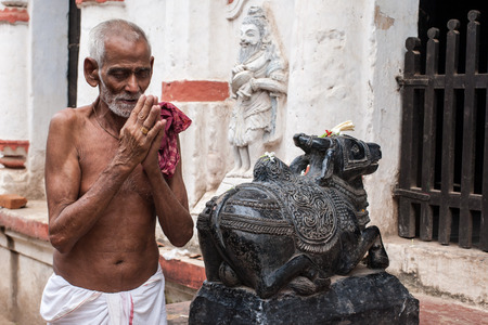 puri: PURI, INDIA OCTOBER 9th 2010 An old man prays outside a temple of Shiva in East India. Editorial