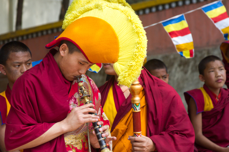 reciting: SWAYAMBHUNATH, NEPAL - MAY 3: A Buddhist monk in traditional Tibetan costume plays an instrument as part of a ritual.