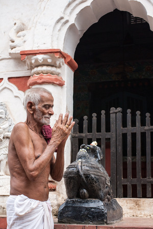 PURI, INDIA, OCTOBER 9th 2010 - An old man praying outside a temple of Shiva in East India. Editorial